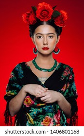Fashion portrait of a brunette woman posing as Frida Kahlo. Red background
