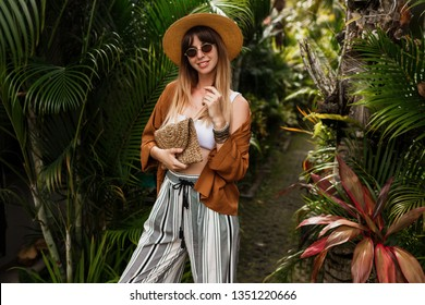 Fashion portrait of brunette woman in straw hat posing on tropical palm leaves background in Bali. Wearing stylish bohemian accessories.