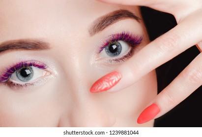 Fashion portrait close-up. Nails manicure and colored fake eyelashes. Eyes wide open.