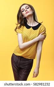 Fashion portrait of confident beautiful woman posing on yellow background