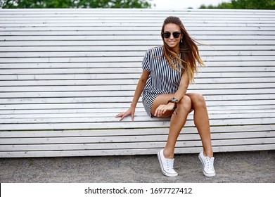 Fashion portrait of cute beautiful woman in sunglasses sitting on a bench