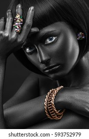 Fashion portrait of a dark-skinned beautiful girl with jewerly. Black Beauty face. Picture taken in the studio on a black background.