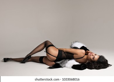 Fashion portrait of elegant brunnette women in studio lying over white background wearing black lingerie, stockings and fur.