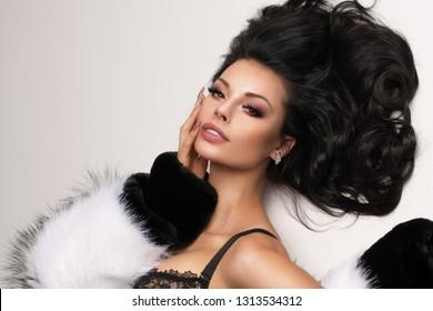 Fashion portrait of elegant brunnette women in studio lying over white background wearing black lingerie, stockings and fur.