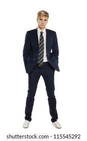 Fashion portrait of elegant young handsome man in full length posing with hands in pockets, over white background