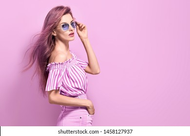 Fashion portrait Enchanting woman with trendy hairstyle, make up in stylish purple Outfit. Beautiful sensual long-haired slim model Girl in Trendy fashionable Sunglasses posing on purple.