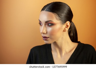 fashion portrait, Eurasian girl with smooth hair, looking into the distance on an orange background, elegant makeup