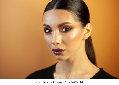 fashion portrait, Eurasian girl with smooth hair, on an orange background, exquisite makeup looks straight into the camera