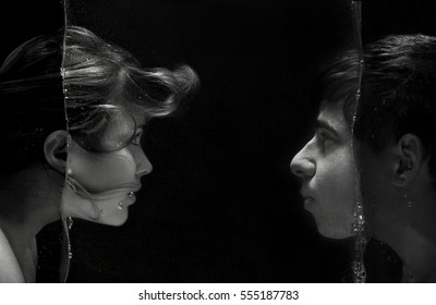 fashion portrait of faces of a young couple separated by a layer of water with the direction of gaze at each other representing fantastic world of relations
