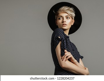 Fashion portrait of female model with blond short hair wear black hat and looking at empty space
