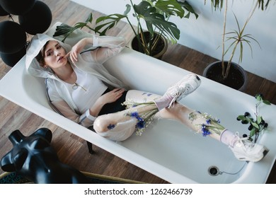 Fashion portrait of girl in plastic trend clothes. Eco styling. Model lying in bath.