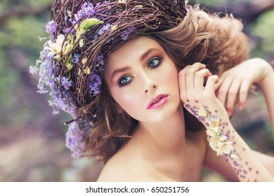 Fashion portrait girl with professional makeup, in branch-wreath. Outdoor