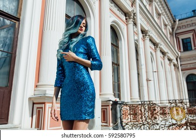 Fashion portrait of gorgeous girl with blue dyed curly hair long. The beautiful evening cocktail dress with strass sequins. Professional makeup and hair styling. Vintage old aristocratic building.