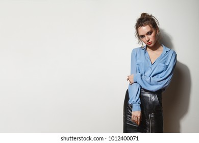 Fashion portrait of gorgeous woman on light background. Free space for text.