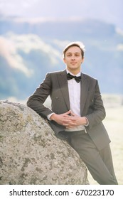 Fashion portrait of the groom in elegant and stylish suit on nature background.