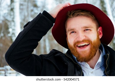Fashion portrait handsome elegant bearded man wearing black coat in winter day over snowy trees forest background