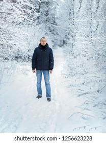 Fashion portrait handsome elegant man wearing a blue down jacket on a winter day against a background of snow-covered trees of the forest, empty copy space