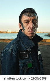 Fashion Portrait of handsome Guy with tattooed Face in denim Jacket on Street