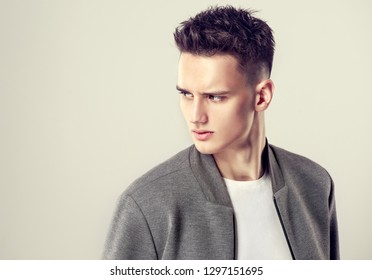 Fashion portrait of a handsome man with a fashionable hair style in a stylish gray  jacket.