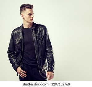 Fashion portrait of a handsome man with a fashionable hair style in a stylish black leather jacket.