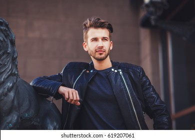 Fashion portrait of a handsome man with hairstyle in a stylish leather jacket