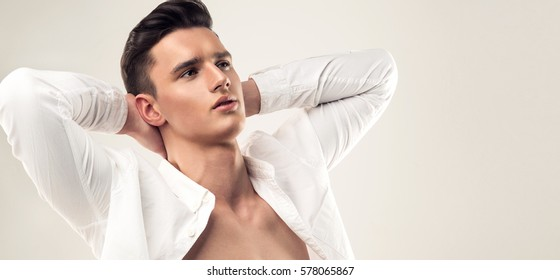 Fashion portrait of a handsome man with trendy hairstyle dressed in a unbuttoned white shirt with dreaming look. Symbol of desire to have perfect vacation and relaxation.