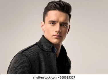 Fashion portrait of a handsome man with trendy hairstyle in a stylish jacket .