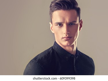 Fashion portrait of a handsome man with trendy hairstyle in a stylish black shirt .