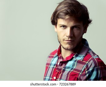 Fashion portrait of a handsome man with trendy hairstyle in a stylish shirt on light green background