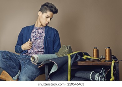 Fashion portrait of handsome young man with tools for sewing denim