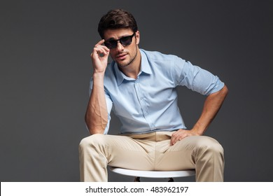 Fashion portrait of handsome young man in sunglasses sitting on the chair over grey background