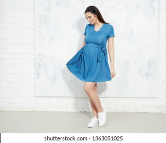 Fashion portrait of happy pregnant woman in blue summer dress against white wall with copyspace.
