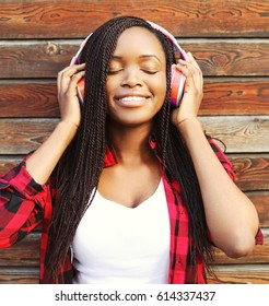Fashion portrait of happy smiling young african woman with headphones is enjoying listens to music