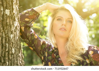 Fashion portrait of happy woman in trendy dress posing in a public garden. Girl with long blonde healthy hair and beautiful smile.