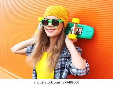 Fashion portrait of hipster cool girl in sunglasses with skateboard having fun outdoors against the colorful orange wall