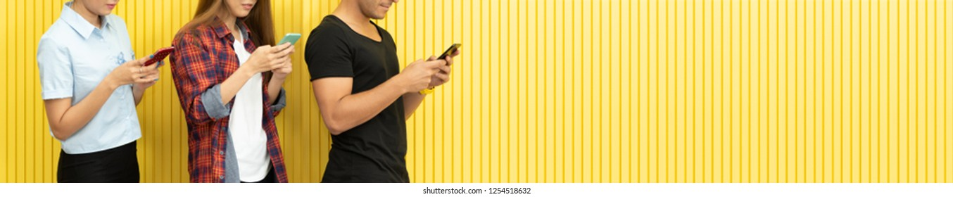 Fashion Portrait of Hipster people are using smartphones and standing over the Yellow wall background. Urban Fashion Concept.
