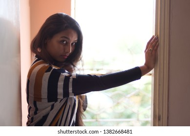 Fashion portrait of an Indian Bengali beautiful and young girl in western dress standing in front of a balcony with ample light leaning on a door frame holding the other side. Indian lifestyle