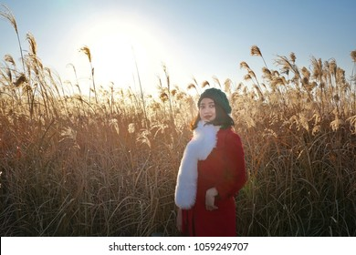 Fashion portrait lifestyle of young Asian woman in grassland and wind wheel with red coat, white fur, green hat. Vintage style tone with the sunshine at Haneul Park, Seoul, Korea