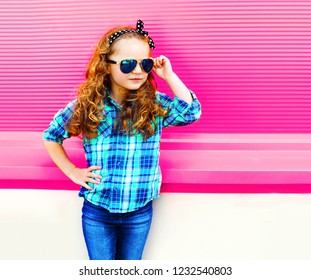 Fashion portrait little girl child in checkered shirt, sunglasses posing on colorful pink wall background