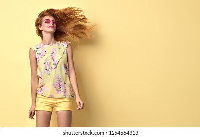 Fashion Portrait lovable woman dance in studio in Stylish blouse, yellow shorts, Trendy wavy hairstyle, fashionable makeup. Redhead model girl with happy positive emotion, dancing concept