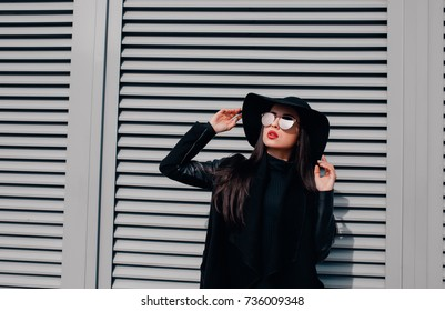 Fashion portrait of lovely brunette woman in glasses and hat posing at the shutters in the city