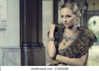 fashion portrait of luxury blonde girl posing with elegant hair-style, fur shawl and precious shiny jewellery. Cute make-up