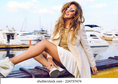 Fashion portrait of luxury sexy blonde girl posing near yacht club in white stylish cashmere coat, golden top sneakers and sunglasses.Bright colors.