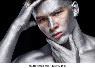 A fashion portrait of man with silver bodyart and face art.