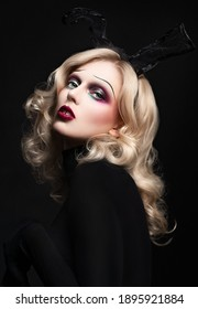 Fashion portrait of model with creative make up posing in studio in rabbit ears