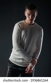 Fashion portrait on a black background of a handsome male model in white blouse and black pants