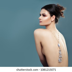 Fashion Portrait of Perfect Woman with Jewelry on Blue Background with Copy space. Female Back and Trendy Gem Jewellery Necklace