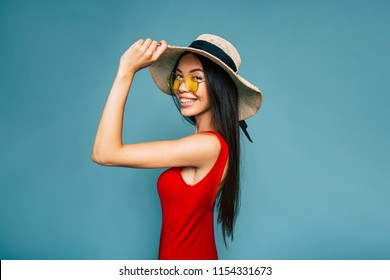 Fashion portrait of pretty asian woman in summer straw hat and sunglasses over colorful blue background