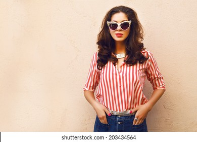 Fashion portrait of pretty brunette posing near wall, wearing bright vintage clothes sunglasses and hairstyle, soft colors.
