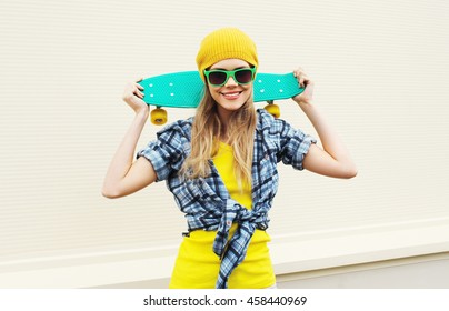 Fashion portrait pretty cool smiling girl with skateboard over white background